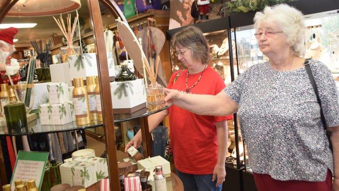 Jerry Rush (left) and Pat Taylor, both of Alexandria, look at items at John Ward Interiors on Small Business Saturday.