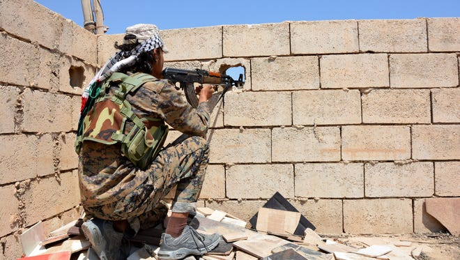A soldier aims an automatic rifle through a peephole in a wall at Raqqa city, Syria, on June, 11 2017.