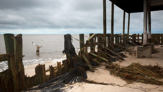 A fisherman throws a cast net near a damaged sea wall in the Alligator Point community of Franklin County, Fla., on Saturday, Sept. 3, 2016. The Category 1 hurricane made landfall near the beach community early Friday morning in the Big Bend area of Florida.