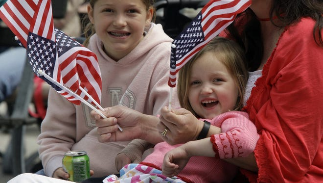 Carolyne van Deventer and her younger sister Lauren are surrounded by flags of the United States while listening to the Sheboygan Pops Band perform a march Monday May 25, 2015, in Sheboygan.