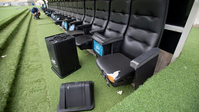 A trash can lays by ripped seats in one of the dugouts in Maracana stadium in Rio de Janeiro, Brazil.