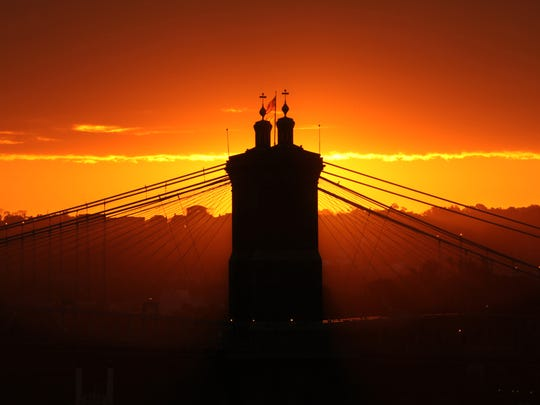 The John A. Roebling Suspension Bridge is in silhouette