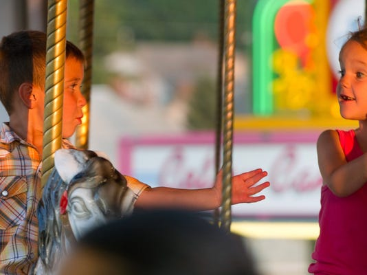 With no hands, Aiden Perry, age 5, left, of Manchester, left, looks over at Laci Lesher, age 6, of Chambersburg while riding the carousel during the Shrewsbury Volunteer Firemen's Annual Carnival Tuesday June 25, 2013 in Shrewsbury. The carnival runs until June 29 with fireworks at 11 the last night. YORK DAILY RECORD/SUNDAY NEWS - PAUL KUEHNEL