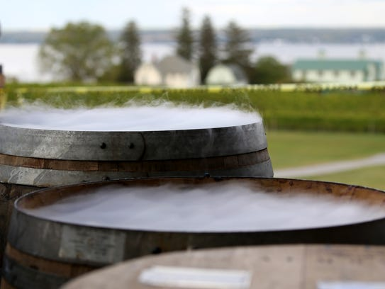Dry ice creates fog at the top of wine barrels during