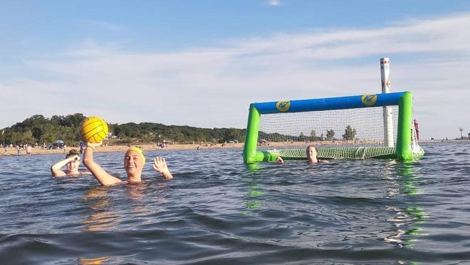 The Zeeland girls water polo team practices on Lake Michigan using inflatable goals.