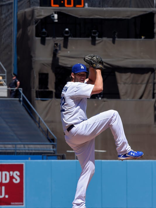 Los Angeles Dodgers starting pitcher Clayton Kershaw warms up as a clock in center field counts down prior to the first inning of an opening day baseball game against the San Diego Padres, Monday, April 6, 2015, in Los Angeles. (AP Photo/Mark J. Terrill)