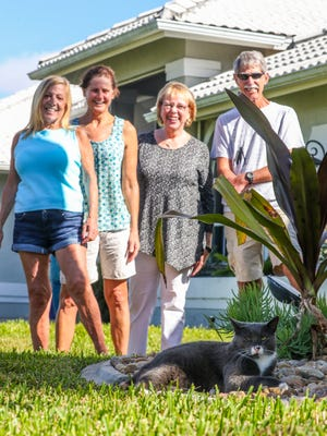 Neighbors Cheryl Kudrna, Darlene Medler, Lenora Marshall, and Bill Medler enjoy taking care of  Louie, the neighborhood cat.  Neighbors on SW 20th Place buy cat food to make sure he's fed, some have spots for him to rest, and they ask for motorist to keep an eye out for him when driving down their street.
