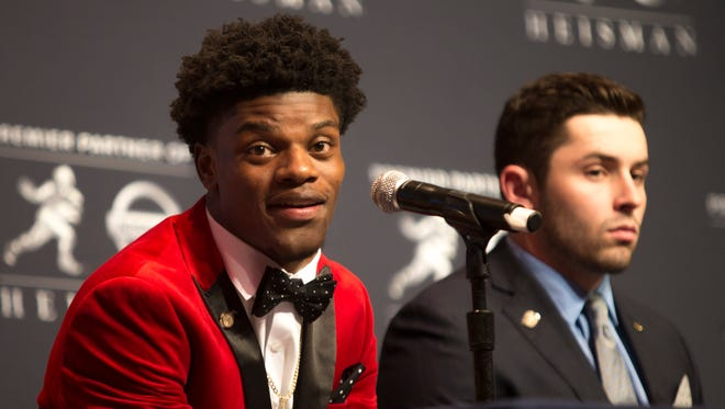 Louisville quarterback Lamar Jackson, left, makes a point during a press conference prior to the Heisman Trophy announcement. Jackson is the favorite to win the award. Dec. 10, 2016