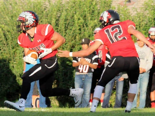 Browning quarterback Derek Loring, right, hands off to twin brother Dylan during a game last fall.