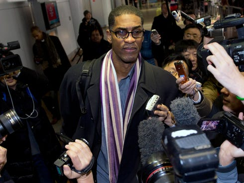Former NBA basketball star Charles D. Smith, center, is mobbed by journalists upon arrival at the Beijing Capital International Airport Friday.