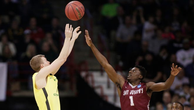Oregon guard Casey Benson, left, shoots against Saint Joseph's guard Shavar Newkirk (1) during the first half of a second-round men's college basketball game in the NCAA Tournament in Spokane, Wash., Sunday, March 20, 2016. (AP Photo/Young Kwak)