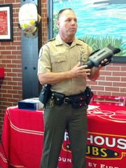 Capt. Mitts Mravic of the Florida Fish and Wildlife Commission, shows off the night vision binoculars from Firehouse Subs.