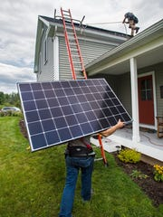Brennan Scott, bottom, and Dave Strippe of SunCommon install solar panels on a house in Shelburne on Wednesday, August 31, 2016.
