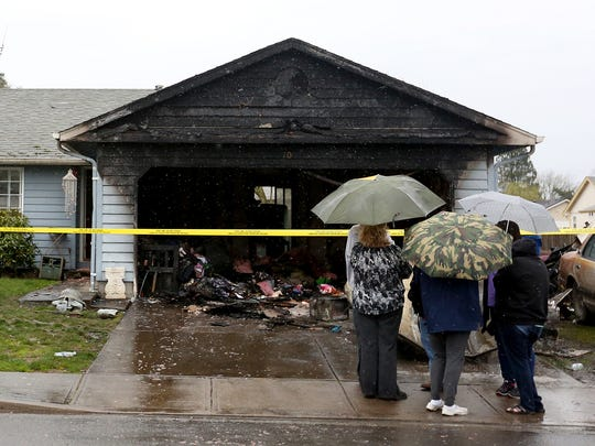 People stand outside after a garage burned at a duplex in Keizer on Tuesday, March 1, 2016.