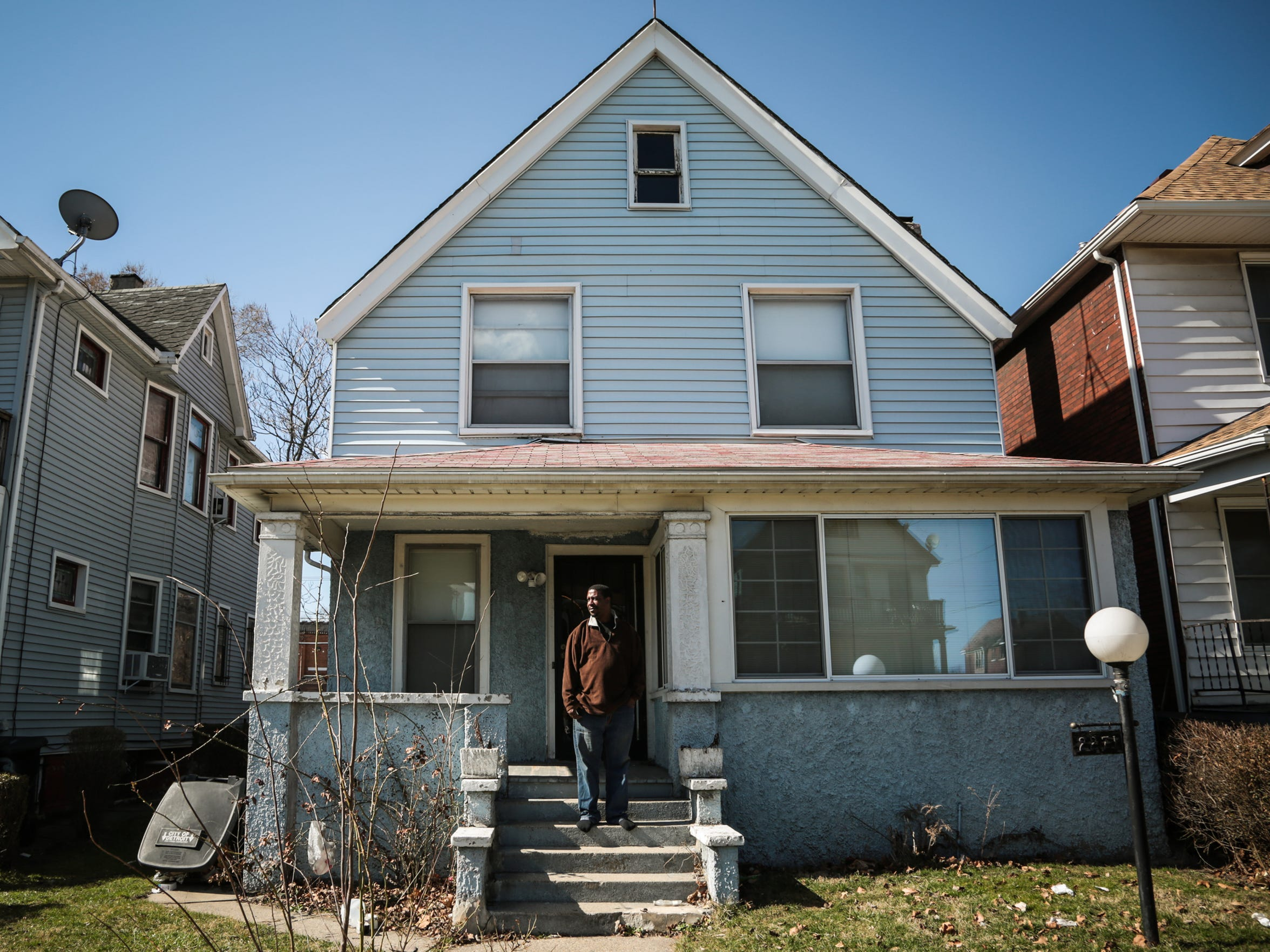 Alonzo Green, 44, of Detroit, stands on the porch of his mother's home on Bewick, on Detroit's east side, on March 8, 2017. Green moved back from North Carolina in January to try to repair his mother's home after she was moved to a nursing home.