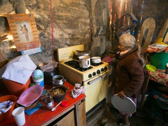 Selerina Guadalupe Villa, 85, boils water in her home