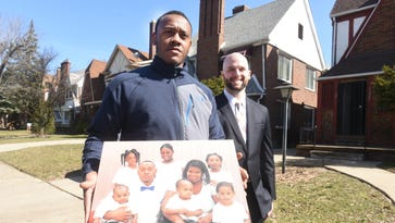 David Prentice, Chairman (right), Home Team, stands with homeowner Shaquille Coleman outside a home on Roselawn Street as he holds a photograph of his family on Tuesday March 21, 2017 in Detroit. The company wants buy thousands of northwest Detroit properties headed for the county tax foreclosure auction.