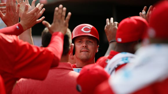 Jay Bruce is greeted by teammates after scoring in the fourth inning of a Cactus League game between the Cleveland Indians and Cincinnati Reds, Tuesday, March 1, 2016, at Goodyear Ballpark, in Goodyear, Arizona.