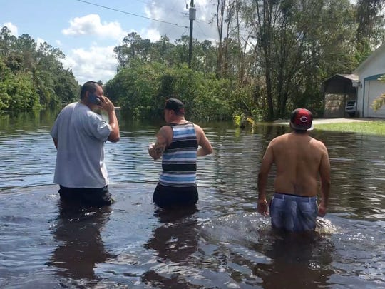 Residents of the Avis Avenue area of Lehigh Acres wade from their homes to a car parked on dry land just off of Buckingham Road on Tuesday after Hurricane Irma.