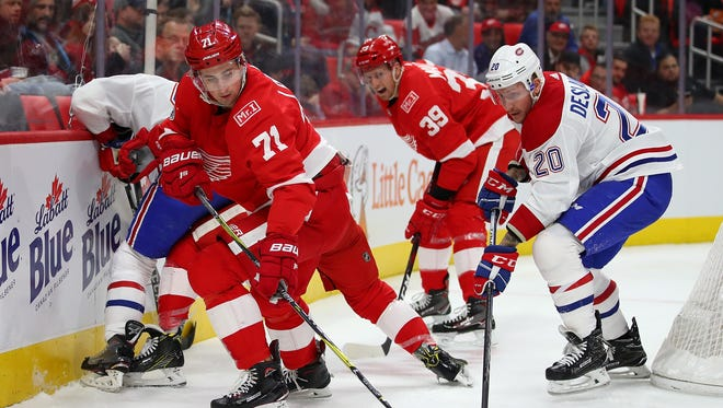 Red Wings center Dylan Larkin battles for the puck with Nicolas Deslauriers of the Canadiens during the first period at Little Caesars Arena on Nov. 30, 2017 in Detroit.