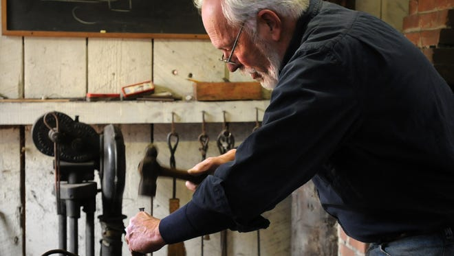 Artisan blacksmith Lee Johnson shows off his craft, making leaf-accented iron candle holders at the Furnace Town Living Heritage Museum.