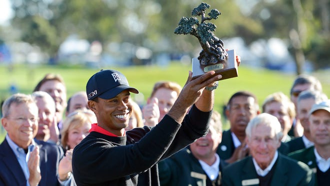 Tiger Woods holds up the Farmers Insurance trophy after winning the tournament by four strokes at 14 under par last year at Torrey Pines.