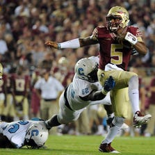 Sep 6, 2014; Tallahassee, FL, USA; Florida State Seminoles quarterback Jameis Winston (5) scrambles away from Citadel Bulldogs defensive lineman Mitchell Jeter (62) during the first half at Doak Campbell Stadium. Mandatory Credit: Melina Vastola-USA TODAY Sports