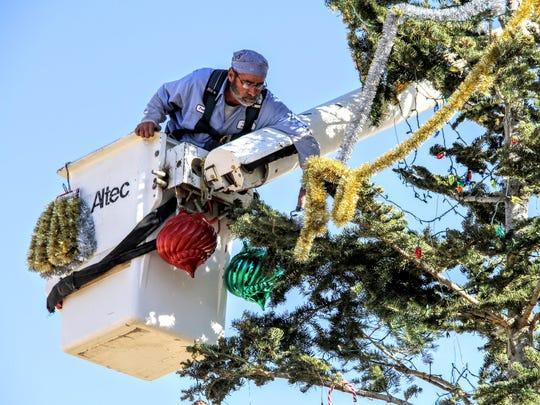 A City employee from the Parks Department hangs decorations on the City's Christmas tree at the Airborne Memorial at 10th Street and White Sands Boulevard on Thursday.
