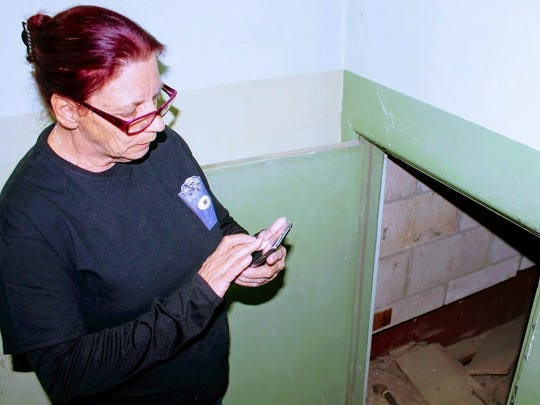 In this Sunday, Feb. 19, 2017 photo, Hidden Haunts Paranormal Investigator Joanne Brandt turns on her cell phone flash light to inspect a small passage way on the third floor of the Everything Outwest vintage store, in Alamogordo, N.M.