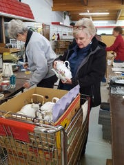 Mary Ellen Johnson and Shary Fiske wrapping housewares.