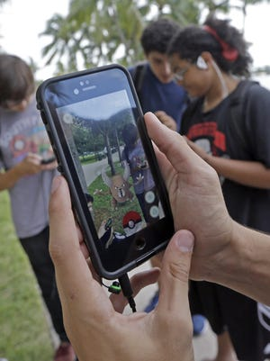 A Pokemon is found by a group of Pokemon Go players at Bayfront Park in downtown Miami.
