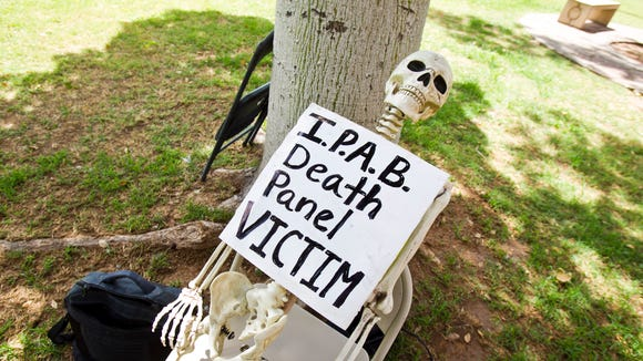 A skeleton wears a sign for the Independent Payment Advisory Board during a referendum rally drive on Medicaid expansion at the State Capitol Building in Phoenix on June 22, 2013.