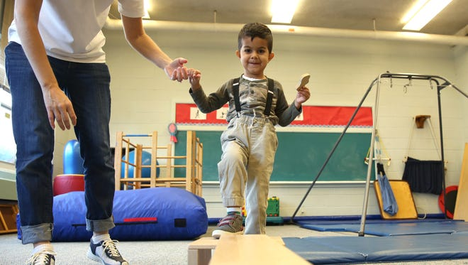 Aarav Kumar practices walking across a beam during a physical therapy lesson with physical therapist Heather Kielkowicz at Liberty Post STARS Preschool.