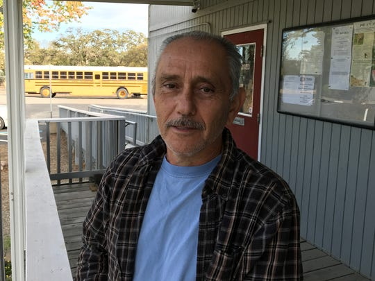 Juan Caravez, president of the  Rancho Tehama Association, talks about Tuesday's shooting. In the background is the bus that was used to remove students from nearby Rancho Tehama Elementary School to the association's recreation hall.