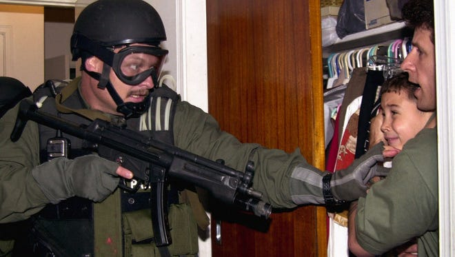 FILE-- Elian Gonzalez is held in a closet by Donato Dalrymple, right, as government officials search the home of Lazaro Gonzalez for the young boy, early Saturday morning, April 22, 2000, in Miami. The armed Border Patrol agent who confronted Elian in this photo said in written after-action debriefing reports released by the Justice Department,  ``While my weapon was being pointed in the general direction I was searching, I never purposely pointed my weapon at Elian Gonzalez or Mr. Dalrymple.''
