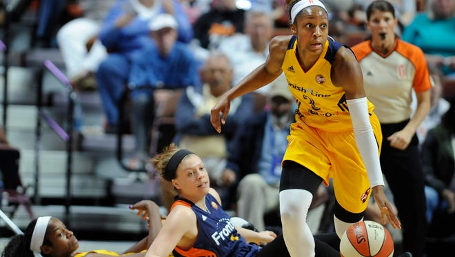 Indiana Fever's Tiffany Mitchell, right, breaks away from Connecticut Sun's Rachel Banham, center, after receiving a pass from fallen teammate Indiana Fever's Devereaux Peters, left, during the first half of a WNBA basketball game, Sunday, June 5, 2016, in Uncasville, Conn. (AP Photo/Jessica Hill)