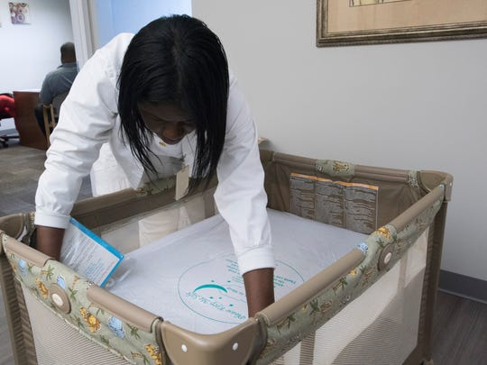 Nurse Deaun Spraglin demonstrates the proper way to make a bed to promote healthy sleeping habits for infants.