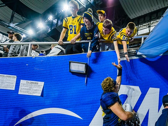 Jared Smith, bottom, of Pewamo-Westphalia high-fives young fans as he walks off the field after the Pirates' Division 7 state final win over Detroit Loyola Saturday November 26, 2016 at Ford Field in Detroit.