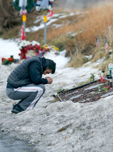 Ryan Damore of Webster prays at the memorial on Lake Road for the West Webster fire personnel. Damore grew up with Firefighter Chiapperini who was like a mentor to him.