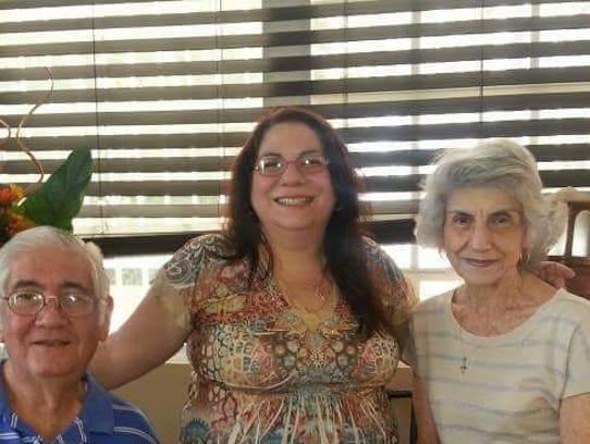 Julie Bolton, center, is seen with her parents, Juan