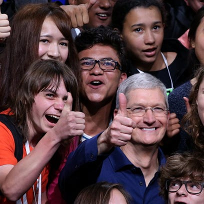 Apple CEO Tim Cook (center) poses for a photo with