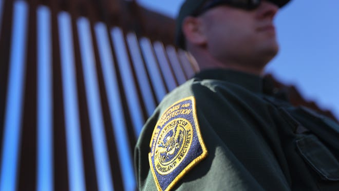 A Border Patrol agent stands at the U.S.-Mexico border fence on February 26, 2013 in Nogales, Arizona.