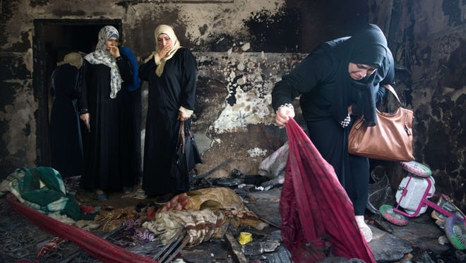 Palestinian women look at the damage at the Dawabsha family's home in the West Bank village of Duma on Aug. 4, 2015, after it was set on fire by suspected Jewish extremists.