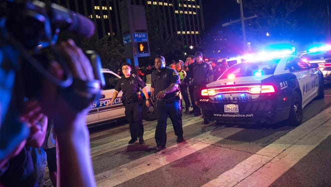 Bystanders stand near police barricades following the sniper shooting in Dallas on July 7, 2016.