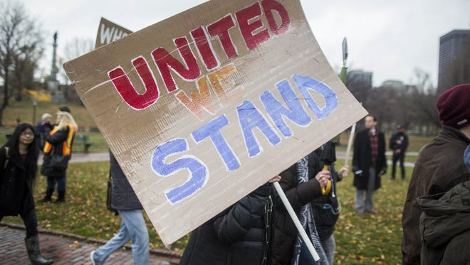 """A protester holds a sign that reads """"United We Stand""""  during a protest by Boston area school students against President-elect Donald Trump after they walked out of classes on Dec. 5, 2016 in Boston, Ma."""