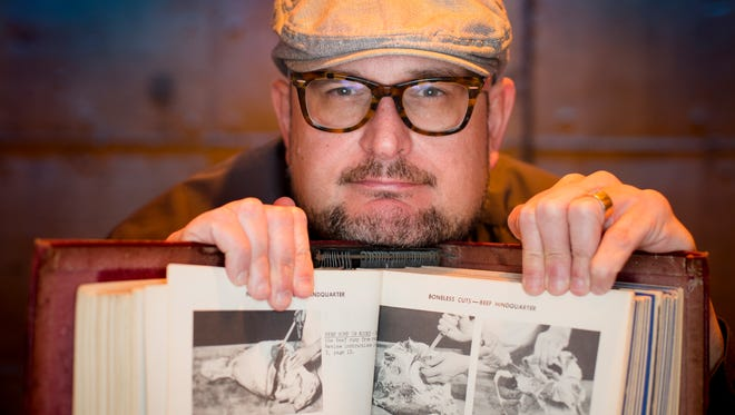 Tue., Jan. 10, 2017:  Jackson Rouse, executive chef of Bauer, is photographed with one of his prized possessions: a vintage a textbook on meat cutting, which he found for $5. His new German farm-to-table will open in the former Jimmy G's space Downtown.
