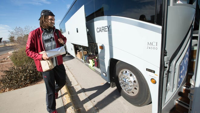 Derek Watson, climbs on to a bus as the New Mexico State University Football team heads to Arizona to play in the Nova Home Loans Arizona Bowl Tuesday Dec. 26, 2017, against Utah State.