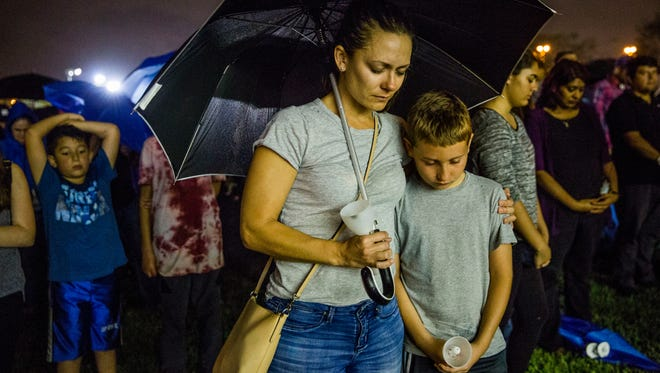 Holly Labarca and her son Oliver, 10, of Coral Springs, bow their heads in prayer during a candlelight vigil at Betti Stradling Park in Coral Springs, Fla., on Monday, Feb. 19, 2018. The vigil was organized by the Florida PTA in response to the shooting at Marjory Stoneman Douglas High School on Wednesday that killed 17 people.