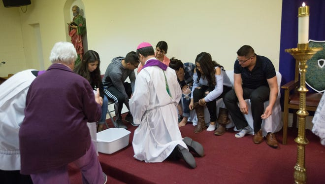 Bishop Oscar Cantú, of the Las Cruces Diocese, with the help of Sister Chabela Galbe, washes the feet of seven DREAMers during a ceremony in February. The bishop this week asked Roman Catholics to come together to provide hospitality to Central American refugees.