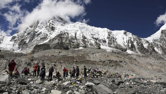 Mount Everest peeks through the clouds in this Sept. 27, 2015, photo, taken from Everest Base Camp in Nepal.